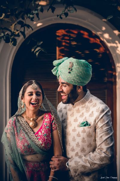 Photo of A bride and groom in color-coordinated outfits laughing on their wedding day