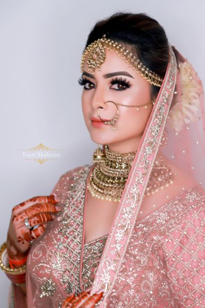Photo of A bride in soft pink lehenga and subtle makeup