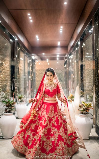 Photo of Red and gold bridal lehenga with zardozi work , twirling bride , red bridal lehenga