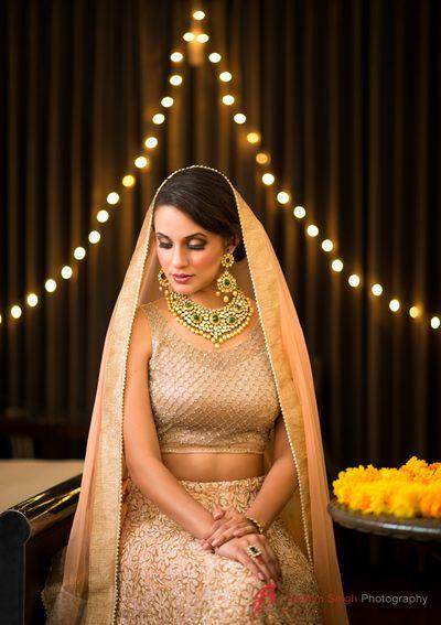 Photo of Bride wearing Peach and Gold Lehenga