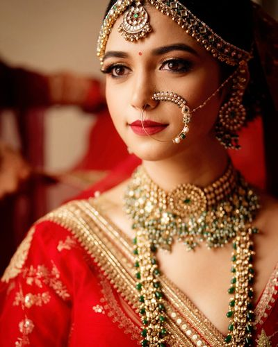 Photo of Bride wearing a red lehenga with polki jewellery.