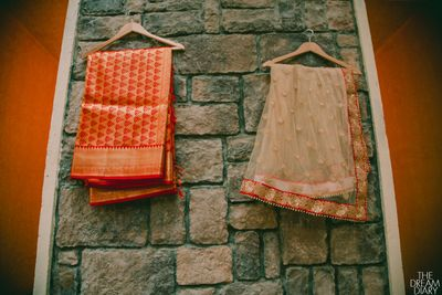Photo of Orange and Gold Saris on a Hanger