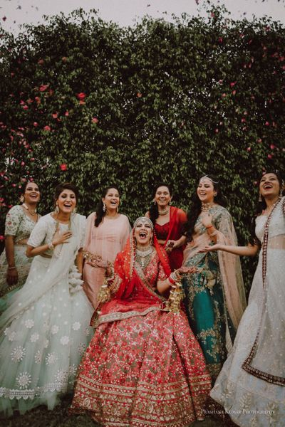Photo of A bride in a red lehenga laughing with her bridesmaids on her wedding day