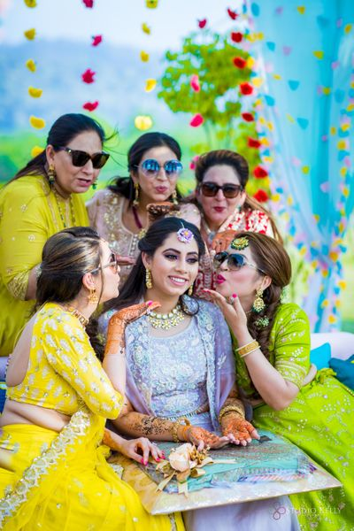 Photo of A bride posing with her bridesmaids on her mehndi