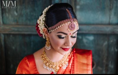 Photo of South Indian bride wearing smokey eyes and red lips.