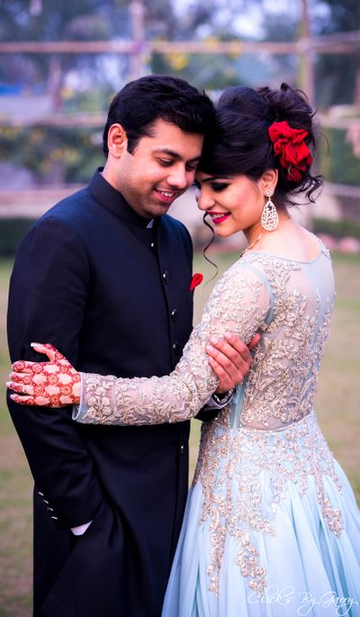 Photo of Engagement look with sheer pale blue gown and red roses in hair