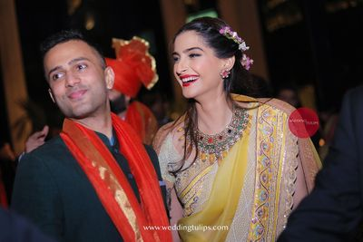 Photo of Sonam kapoor and anand ahuja at moht marwahs wedding in a yellow anamika khanna saree