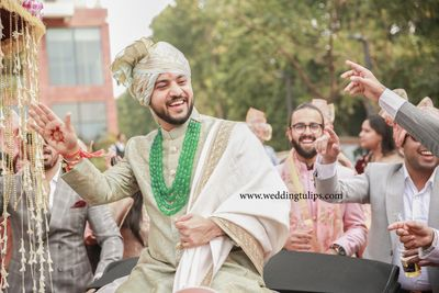 Photo of Groom wearing a heavily beaded green necklace