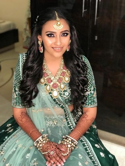Photo of A bride in a green lehenga with chunky necklace