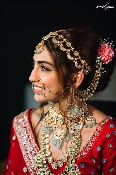 Photo of Brude wearing a pastel jewellery necklace with red lehenga