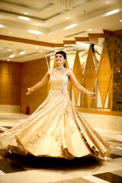Photo of Bride twirling in beige lace gown