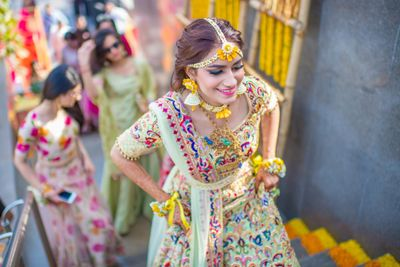 Photo of Mehendi bridal look with floral jewellery and threadwork lehenga
