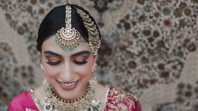 Photo of Bride wearing pink outfit with contrasting jewellery in green.