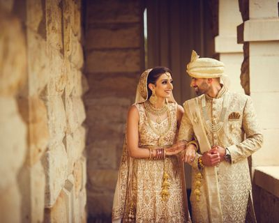 Photo of Colour coordinated bride and groom in ivory outfits
