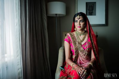 Photo of Bride in neon pink lehenga wearing layered necklace