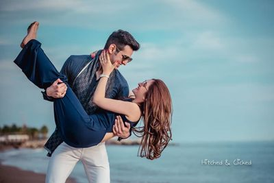 Photo of romantic honeymoon shoot idea with groom picking bride