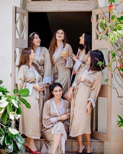 Photo of bride and bridesmaids wearing matching robes for bachelorette