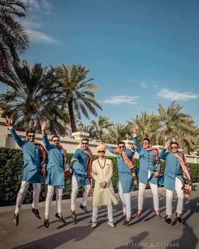 Photo of fun groom and groomsmen photo with all of them in blue sherwani