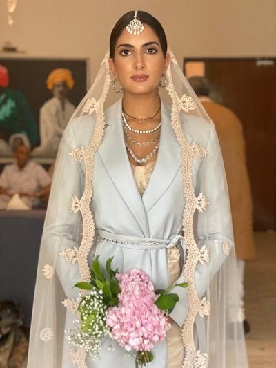 Photo of Millennial bride in a pantsuit with a dupatta as a veil