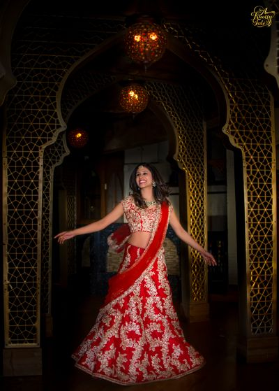 Photo of twirling bride in red and gold lehenga