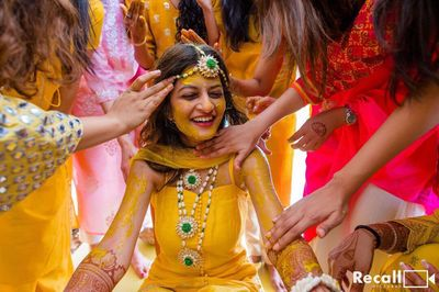 Photo of fun haldi bridal portrait with everyone putting it on her