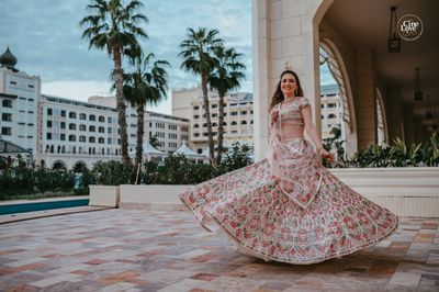 Photo of bride twirling in a pretty pastel mehendi lehenga