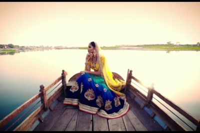 Photo of Unique bridal lehenga with yellow blouse and green and blue skirt