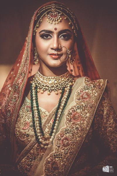 Photo of Bride wearing floral embroidered lehenga and layered choker