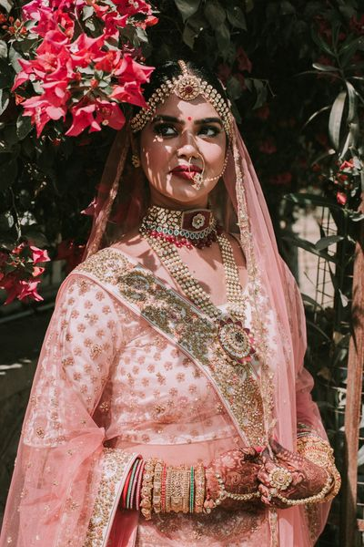 Photo of A bride in a light pink lehenga with layered jewellery