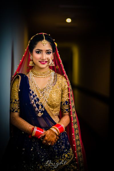 Photo of Bride in blue bridal lehenga with red dupatta and satlada