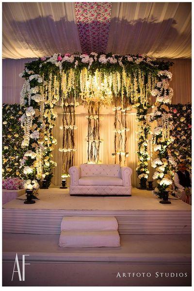 Photo of White theme floral stage decor