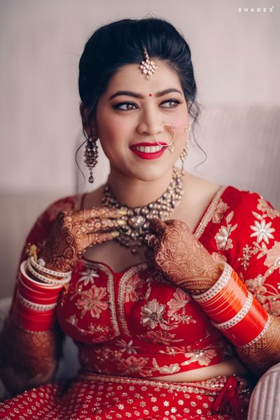 Photo of A bride in red getting ready on her wedding day