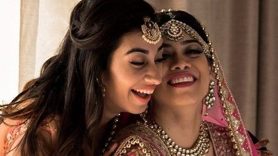 Photo of A bride all decked up for her big day laughing with her sister
