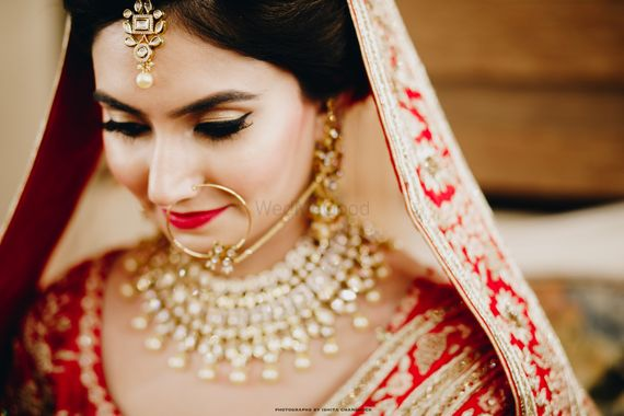 Photo of Bridal makeup with red lips and winged liner
