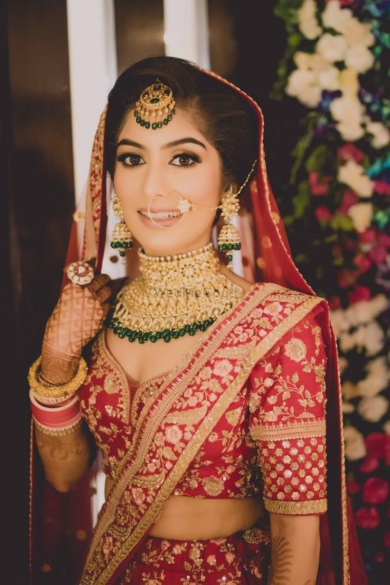 Photo of Bride in red with green contrasting jewellery