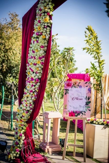 Photo of Floral arrangement at mandap entrance with pheras board