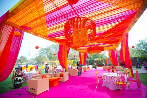 Photo of fuschia and orange theme mehendi decor with floral chandeliers