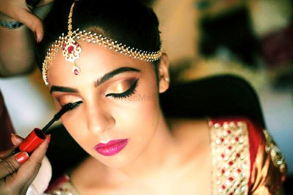 Photo of Bridal makeup with gold eyes and bright pink lips and mascara