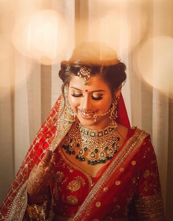 Photo of Shy bride in red lehenga with green jewellery