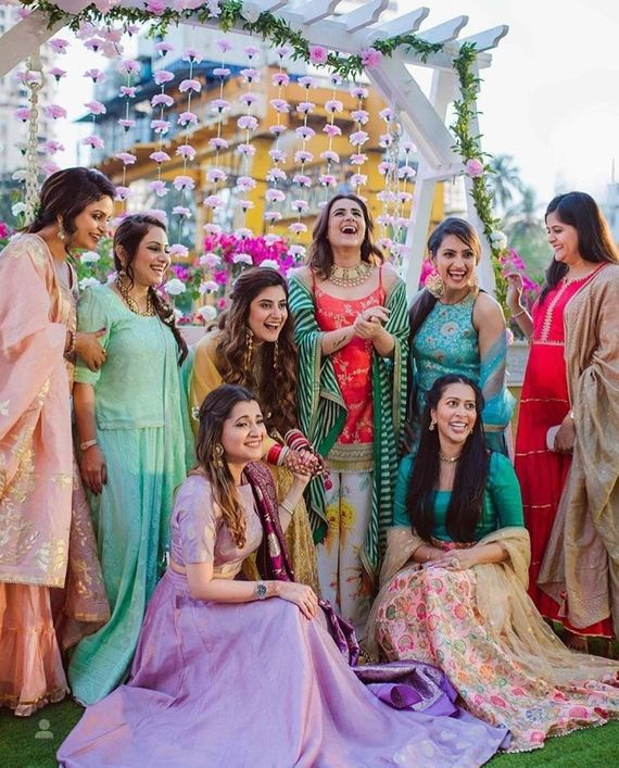 Photo of Bride with bridesmaids in intimate mehendi
