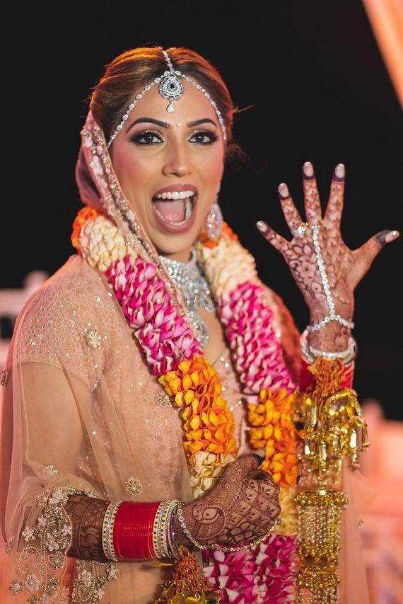 Photo of A bride in pink lehenga with unique jaimala