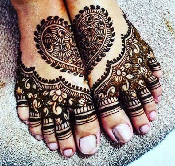Photo of Half and half mehendi design on feet with heart