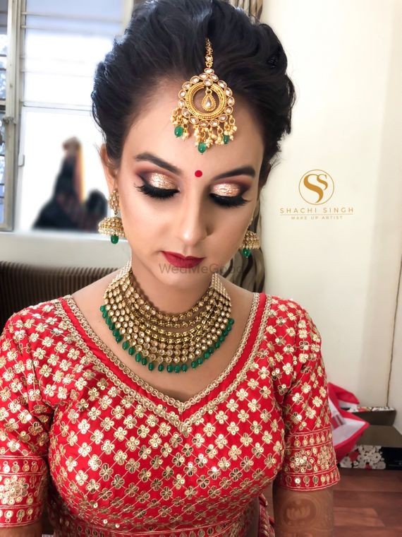 Photo of Pretty bride in red embroidered blouse with gold jewelry