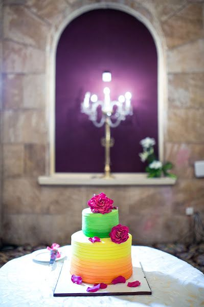 Photo of Colourful wedding cake with different layers and flowers