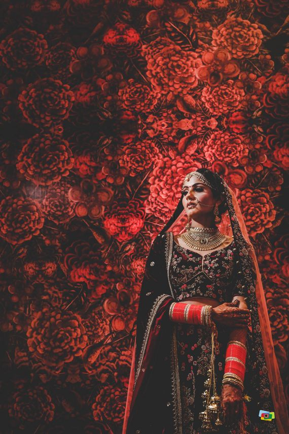 Photo of bride in floral maroon lehenga against floral wall