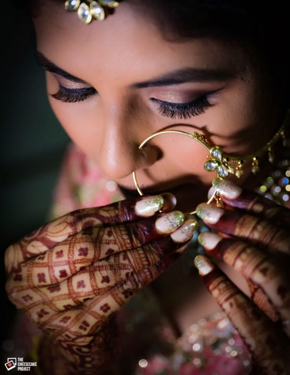 Photo of Bride getting ready shot adjusting nosering