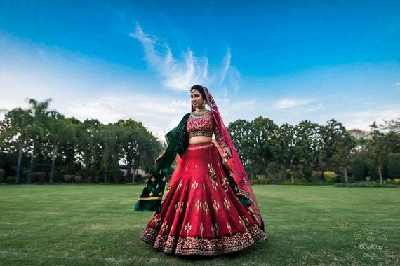 Photo of Bride twirling in red lehenga