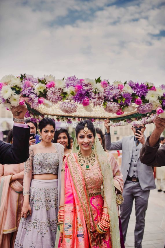 Photo of Bride entering her wedding in lehenga in paithani silk under a floral chaddar