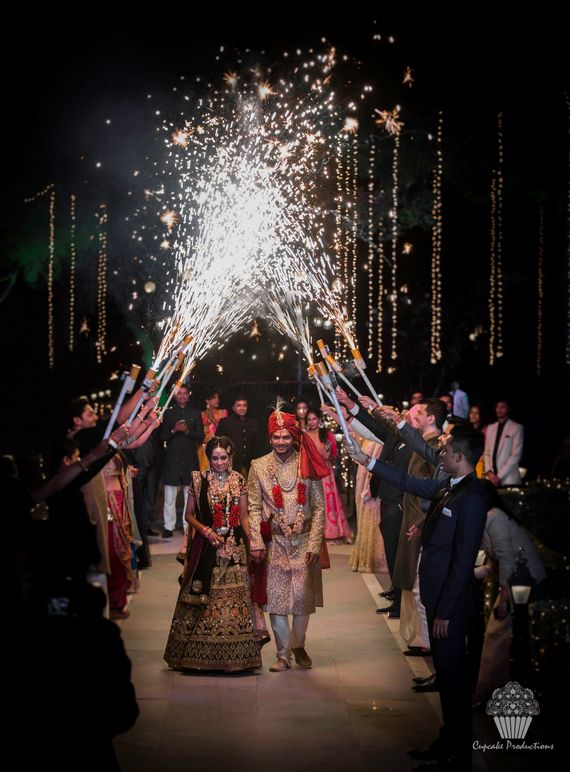 Photo of Couple entering in red with guests holding cold pyros