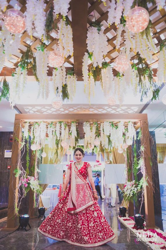 Photo of White and pink theme hanging floral strings and fairy lights wedding entrance decor